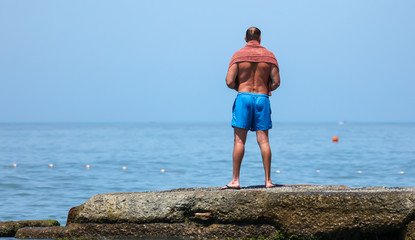 A man stands on the beach. Beach holiday
