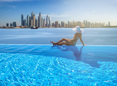 Beautiful panorama of Dubai Marina skyline in a background with a pool, deck chair and woman with a white hat.