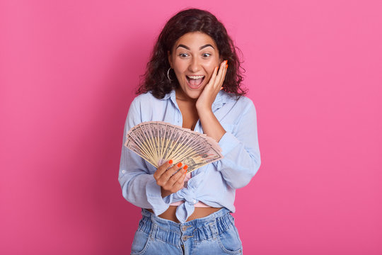 Image of beautiful brunette woman dressed in blue shirt and jeans, smiling and holding bunch of money bills isolated over pinkbackground, keeps mouth opened, has astonished facial expression.