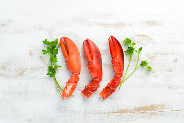 Lobster claws. Seafood on a white wooden background. Top view. Free copy space.