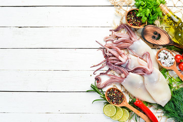 Raw fresh squid with spices. Seafood on a white wooden background. Top view. Free copy space.