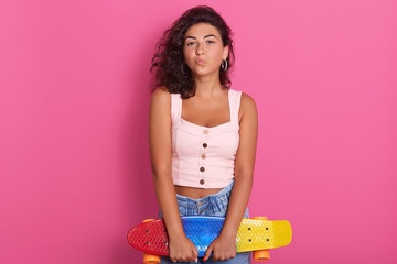 Image of slender sporty young girl keeping her lips folded, holding skatebord in both hands, having curly hair, wearing stylish top and jeans, standing isolated over pink background in studio.