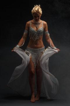 Slender girl blonde in a beautiful costume dancing Oriental dance.