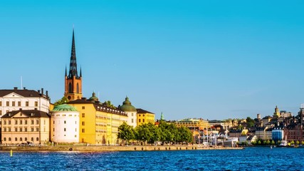 Wall Mural - Stockholm, Sweden. Time-lapse of Gamla Stan in Stockholm, Sweden with landmarks like Riddarholm Church during the sunny summer day. View of old buildings, panning video