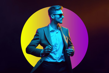 Young handsome model posing in a studio in a trendy neon light. Fashionable man in a stylish suit. Vibrant color. Bright colorful light effects. Disco style. Overlay. Gel filter. Supersaturated
