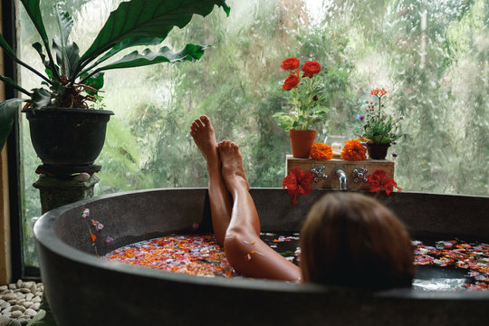 Back view woman relaxing in round outdoor bath with tropical flowers, organic skin care, luxury spa hotel, lifestyle photo. Female legs in bathtub with flower petals