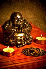 Wall Mural - Happy Buddha and yin yang with candles like oriental spiritual belief