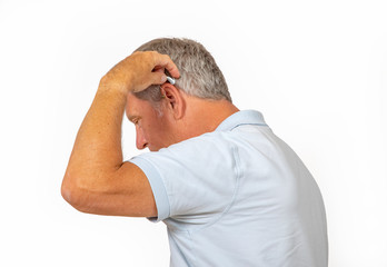 portrait of trustful smiling mature man handling his hearing aid