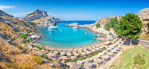 Lindos – panoramic view of St. Paul bay with acropolis of Lindos in background (Rhodes, Greece)