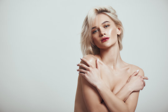Feeling sexy. Beautiful and slim woman with blond hair covering her breast with her hands and looking at camera while standing against grey background