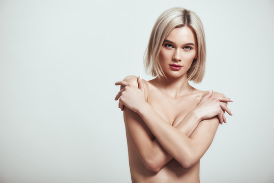 Topless female. Sexy slim woman with blond hair covering her breast with her hands and looking at camera while standing against grey background