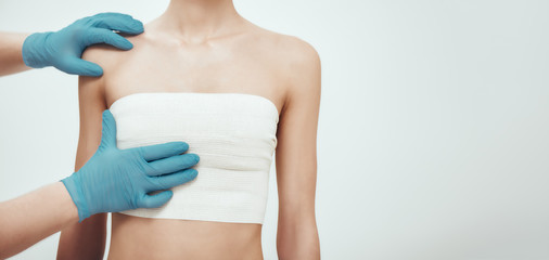 Increase your breast size. Cropped photo of woman waiting for plastic surgery while surgeons in blue medical gloves measuring her breast