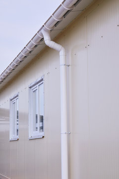 White plastic rain guttering system. Guttering drainage pipe exterior. Background of sandwich panel