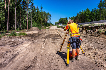 Surveyor engineer (worker) with equipment (theodolite or total positioning station) on the construction site of the road or highway Wall mural
