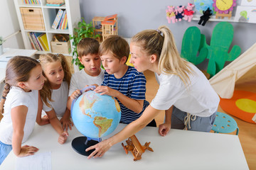 Teacher with School Children Making Geography Lessons Fun and Interesting. Learning Through Play.