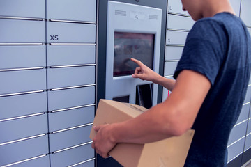 Fototapeta Client using automated self service post terminal machine or locker to deposit a parcel for storage obraz