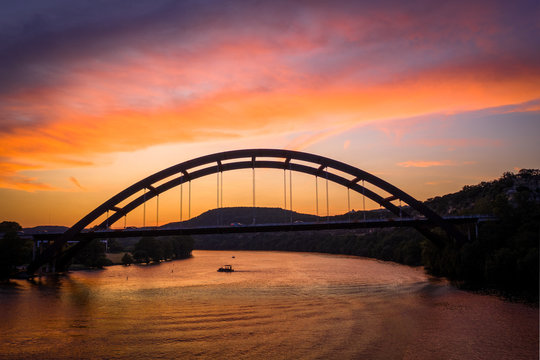 Colorful Pennybacker Bridge Sunset from over River with mountains in the background and a boat on the lake | texas landmark