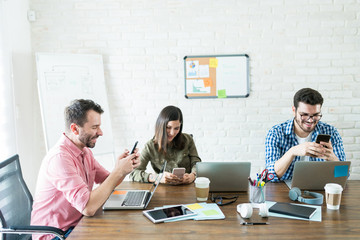 Professionals Socializing While Getting Distracted In Office