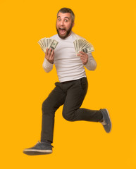 Excited man holding cash and jumping in the air