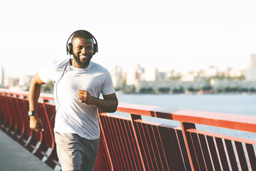 Cheerful black man running along the bridge, listening to music Wall mural