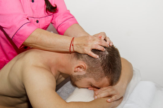 professional therapeutic neck and head massage. man the athlete in a massage room. pain recovery procedure. Female physiotherapist doing manipulative spine treatment on young patient
