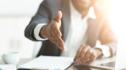 African businessman gives hand for handshake proposes partnership