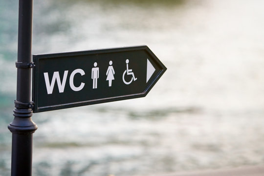 WC logo, sign of public toilets in the street against water background. For female, male and disabled people. Toilet, washroom and bathroom