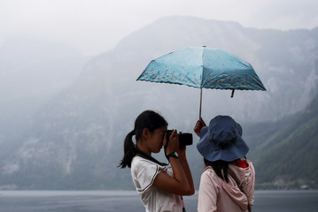A tourist takes a photo of Hallstaettersee lake in Hallstatt