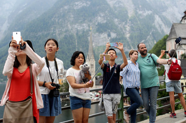 Tourists use their smartphones to take pictures near Hallstaettersee lake in Hallstatt
