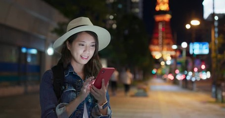 Wall Mural - Woman use of mobile phone in Tokyo city at night