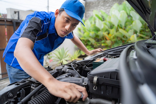 home service mechanic doing some inspection on car's engine