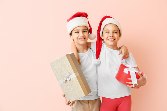Happy little children in Santa hats and with gift boxes on color background