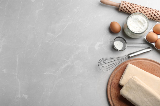 Puff pastry dough and ingredients on grey table, flat lay. Space for text