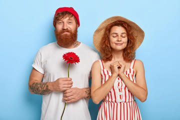 People, closeness, love concept. Handsome bearded red haired boyfriend has date with sweetheart, holds gerbera, knows women like flowers. Pleased lady in summer hat, dress spends free time with lover
