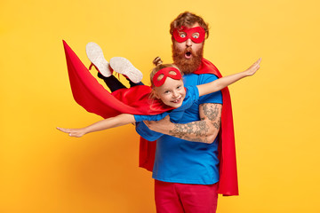 Image of ginger father and daughter dressed in superheroes, surprised man carries little kid on hands, pretend flying and saving world, pose against yellow background. Childhood and fun concept