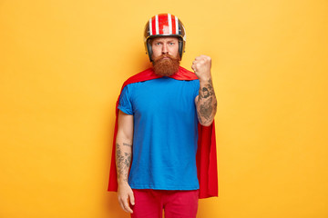 Earnest bearded man clenches fists, shows strength, ready to revenge evil for bad things, wears cartoon costume, pretends being superhero, has power in his hands, isolated on yellow background Wall mural
