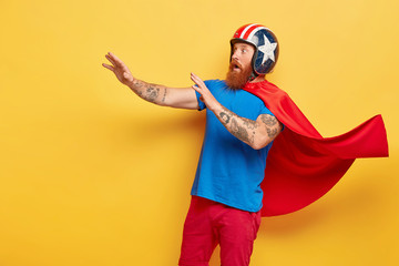 Fearful man wears red cape and helmet, gestures with defense, tries to protect himeself from something terrible, plays extreme game, models on yellow wall. Frightened superhero fights with evil