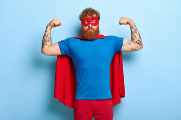 Successful hero wears red mask and cape, raises arms, shows biceps, demonstrates courage and strength, looks serious and confident, poses against blue wall. Real superhero ready to help you.