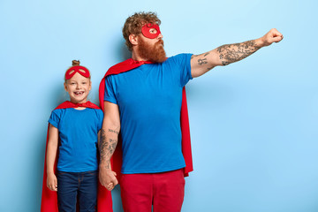 Horizontal shot of feraless strong ginger father holds hand on small kid, stretches arm and shows flying gesture, wears superhero costume, defends daughter and other people, play game together Wall mural