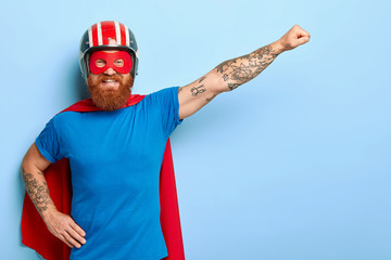 Positive bearded man has cheerful expression, keeps arm outstretched, clenches fist, ready for flight, dressed in helmet blue t shirt and cape imagines being superman uses special power to help people