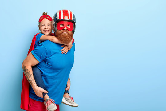 Horizontal shot of caring father gives piggyback to small child, play interesting superhero game, wear special costumes, pose against blue background with free space, have great impact on world