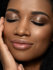 Young beautiful black woman touching her face
