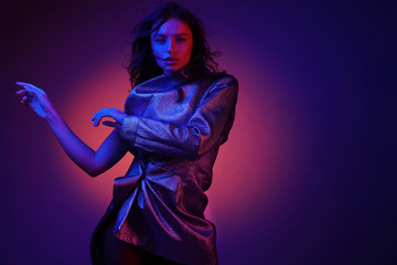 Fashion model in stylish clothing on color neon lights in studio Wall mural