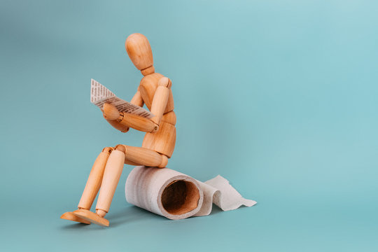 Wooden figure sit on a roll of toilet paper and reading the newspaper