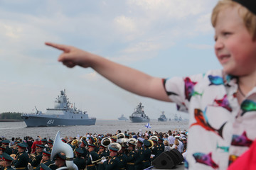 A boy points as Russian warships sail during the Navy Day parade inKronstadt