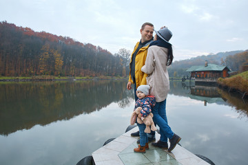 Happy family walking on the wooden pier by the lake in the autumn park.