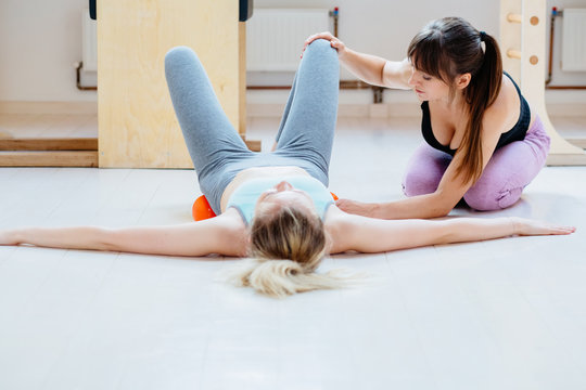 Female instructor helping for client doing self-massage technique applying special balls for back pain relief, working out on floor at pilates studio floor.
