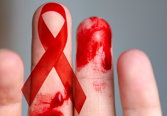 Finger with Blood and Red Ribbon - as Symbol of Supporting and Hope -conceptual Picture about situation with HIV and AIDS in the World