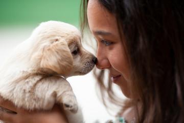 Niña con cachorro de Golden Retriever. Complicidad. Mascota.