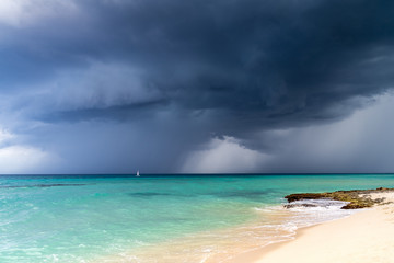 Dramatic view of dark grey storm clouds against the turquoise blue water of the Caribbean sea and a white sand beach